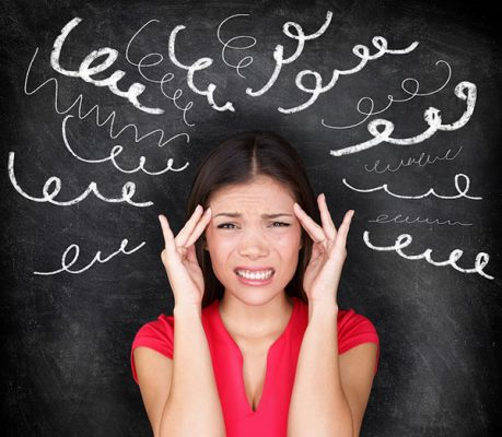 woman with her fingers to her temples distressed in front of a chalkboard with squiggly lines drawn around her head
