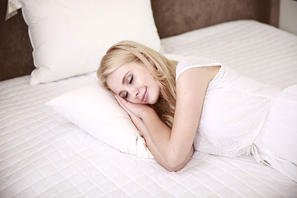 blonde woman laying on a white bed wearing a white dress sleeping