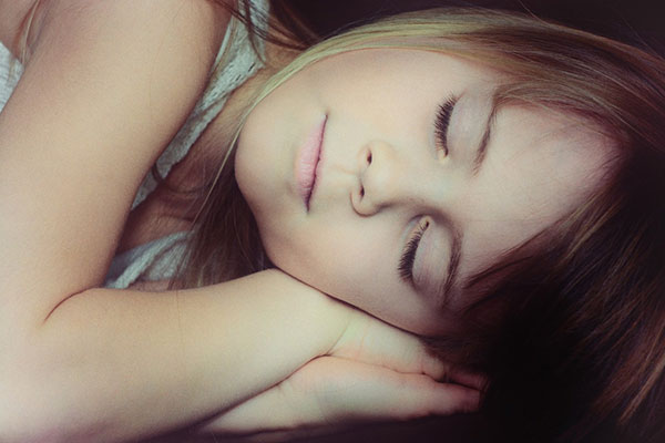 girl laying on her side sleeping with her head resting on her hands