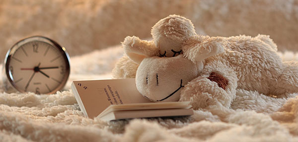 stuffed animal laying on a book in bed as if it's reading next to a clock