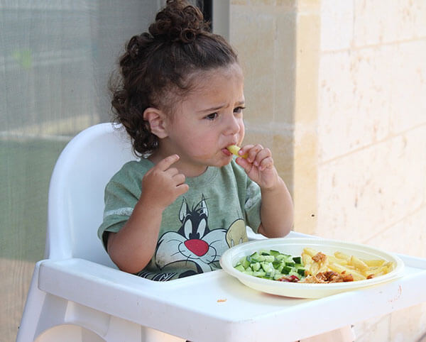 a toddler sitting in a high chair eating food