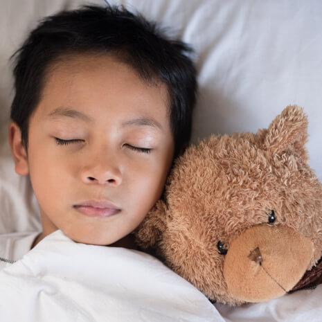 young boy sleeping in bed with a teddy bear next to him