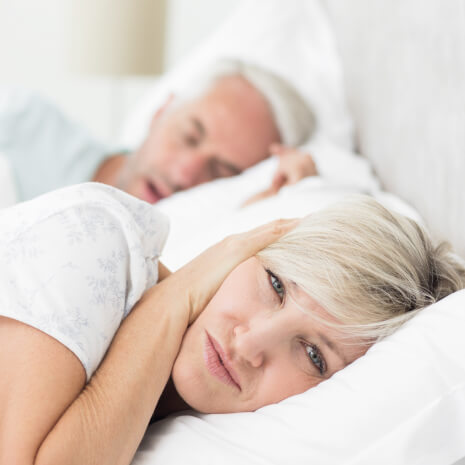 older woman laying in bed holding her hand over her ear as her husband snores
