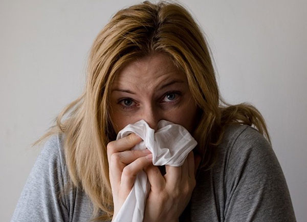 blonde woman blowing her nose wearing a grey shirt in front of a white wall