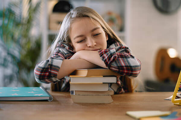 A young girl with her eyes closed, looking sleepy, resting her cheek on her folded arms on a stack of books