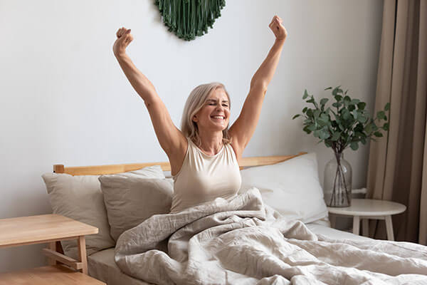 A smiling woman just waking up, stretching her arms over her head
