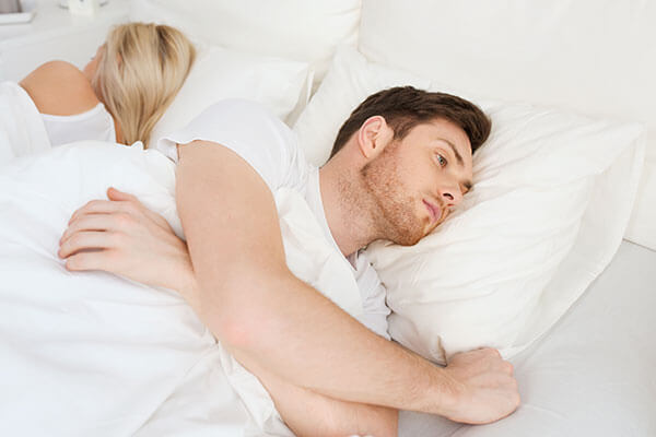 A couple laying in bed with their backs to each other, looking unhappy